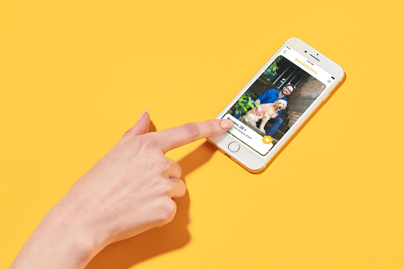 A hand swiping on the Bumble dating app.