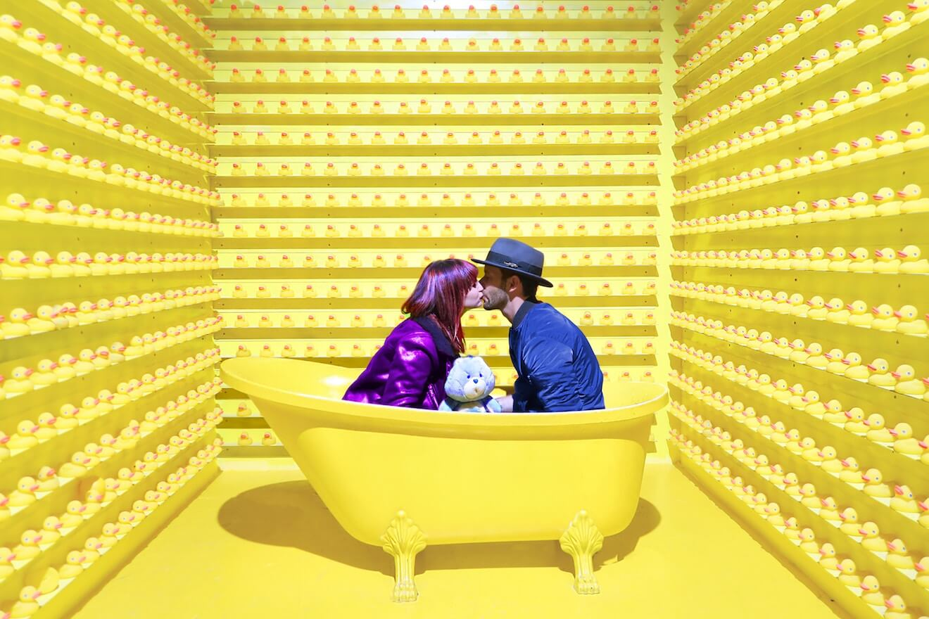 A couple holding a Care Bear kisses in a bathtub surrounded by rubber ducks