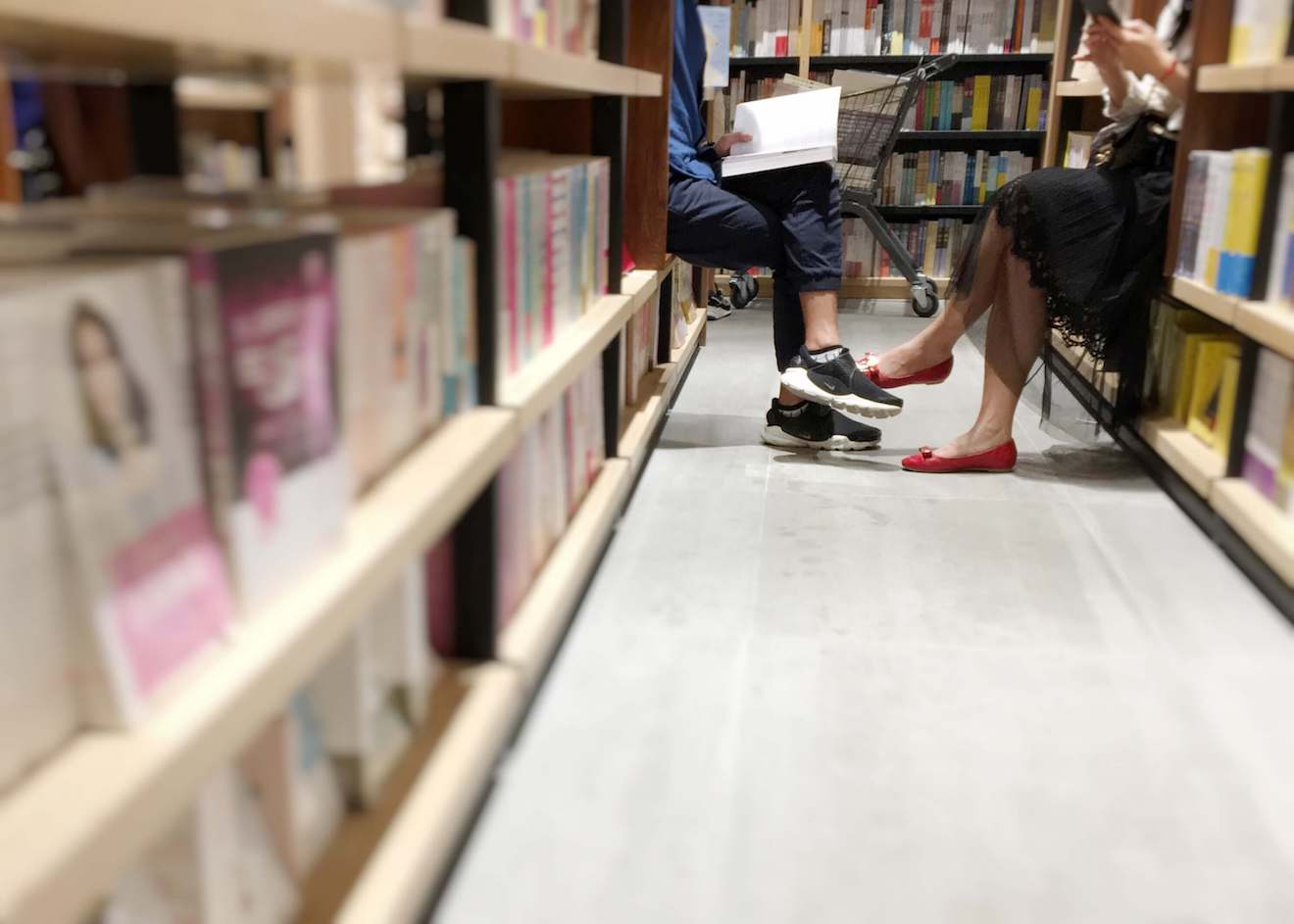 Bookstore patrons read books in the aisle