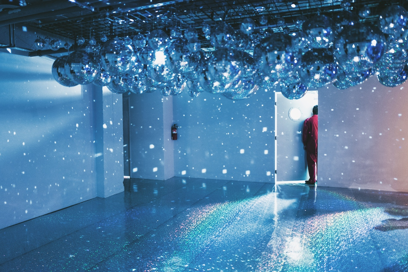Man standing in doorway under disco balls