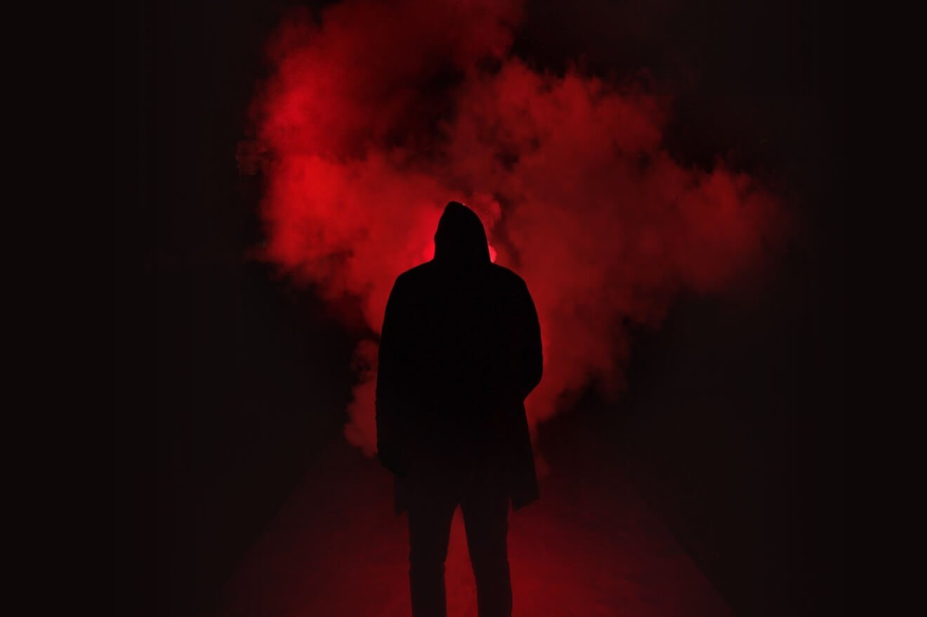 A man's silhouette in front of red smoke at night