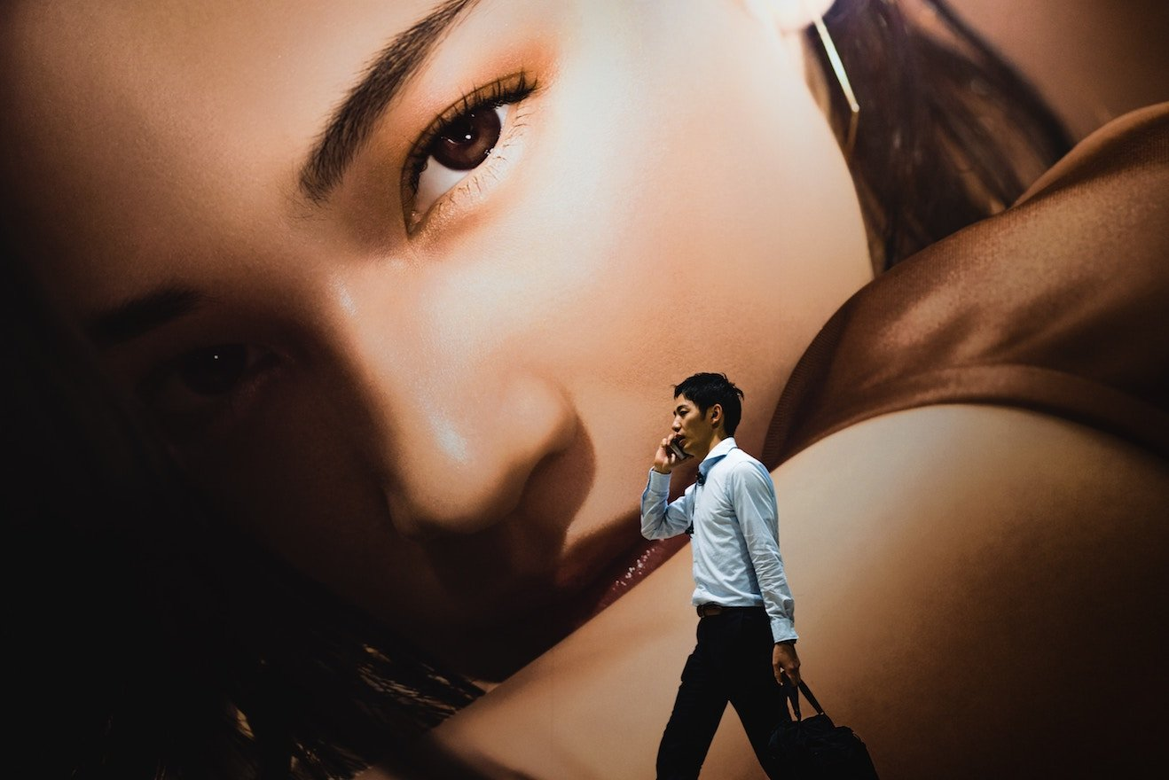 Billboard of woman towering over man on his phone