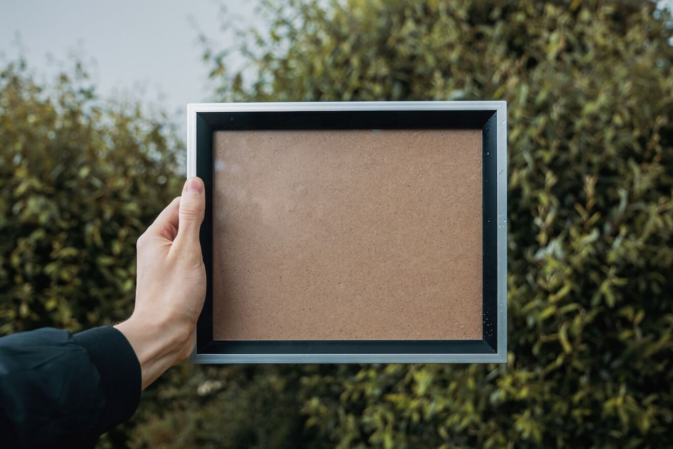 A woman holds a blank picture frame in front of trees