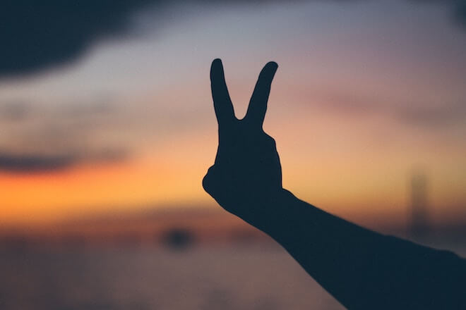 A hand giving a peace sign to the sunset