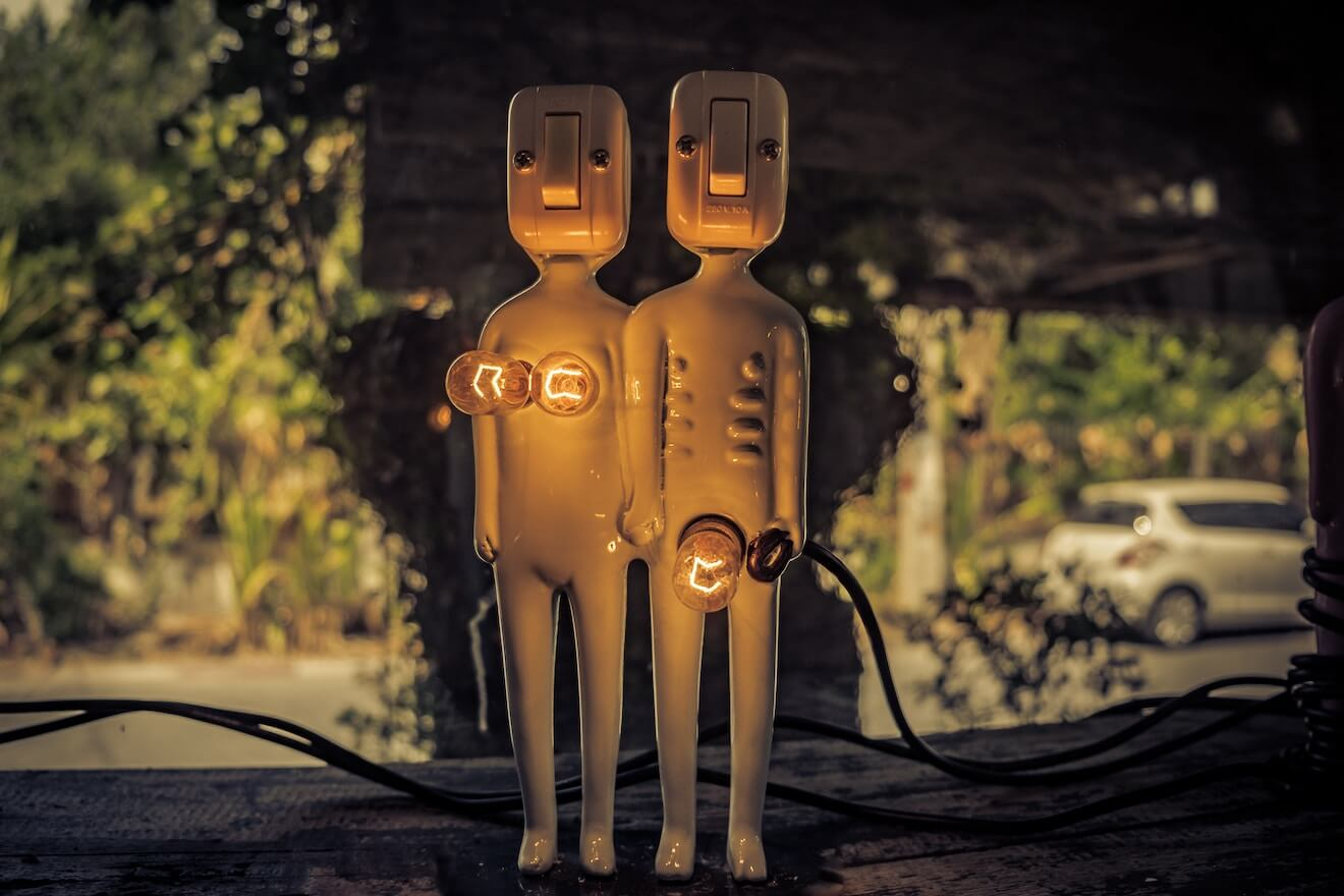 "Two wooden figures with lightbulbs for naughty bits ""turned on"""