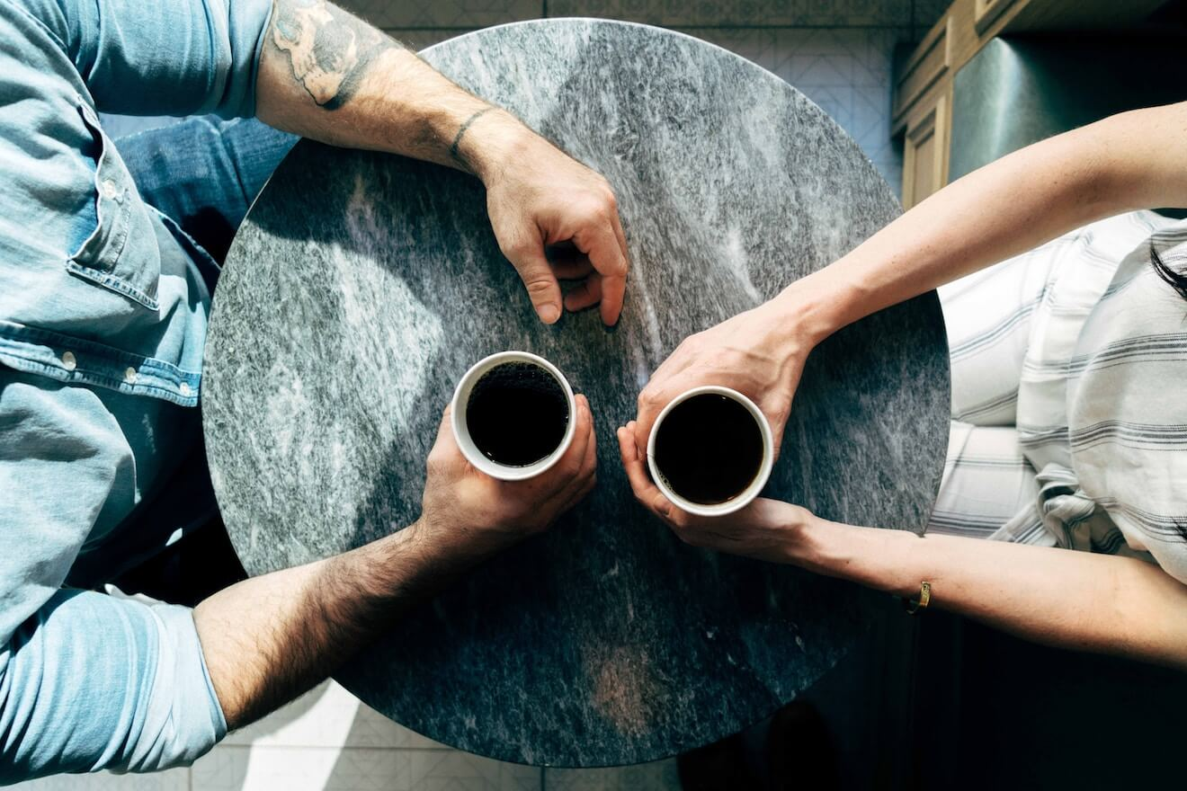 Two people having coffee sitting across from each other