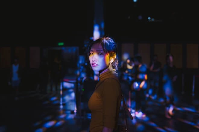 A woman looks pensive in the dark with colored light around her body