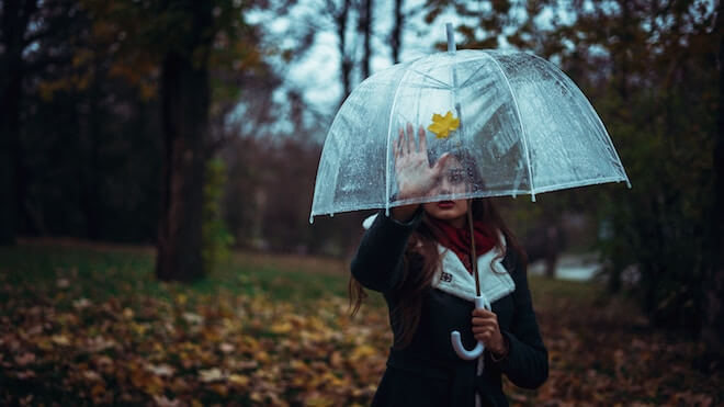 A woman with a clear umbrella reaches out to a yellow leaf