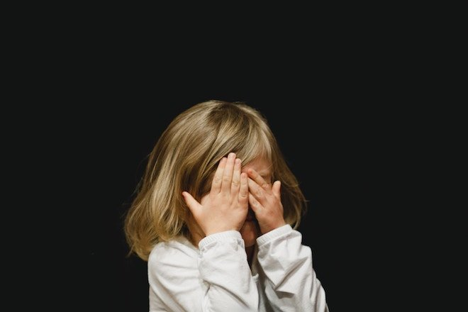 A girl covers her eyes in front of a black background