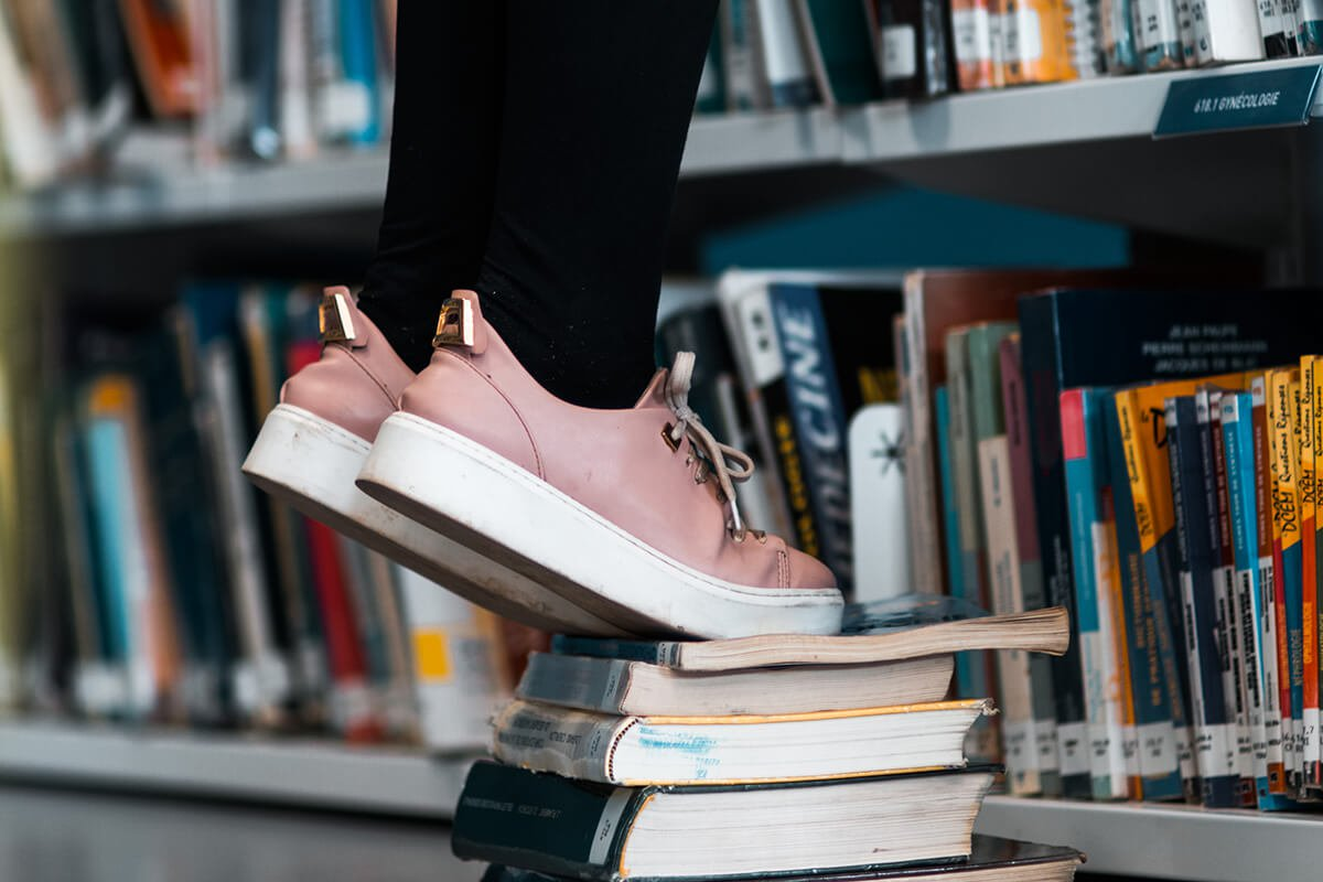 Standing on tip toes on stack of books