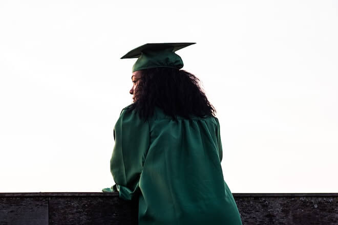 A woman stands over a balcony with a graduation cap and gown on