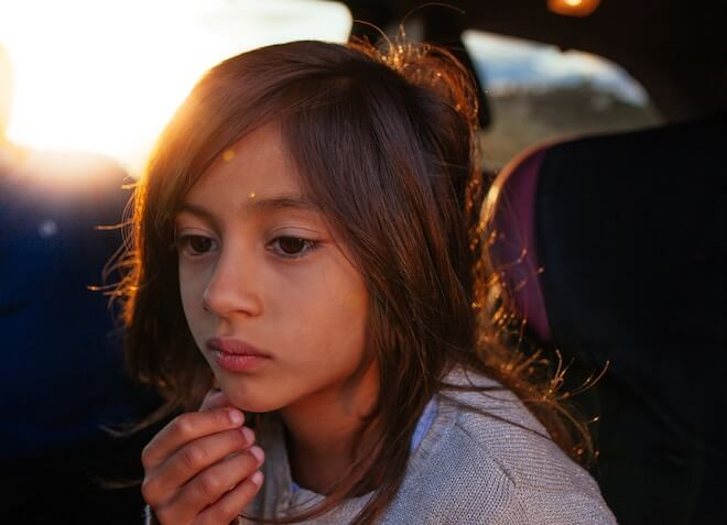 A child looks forlorn with a sunset in the background