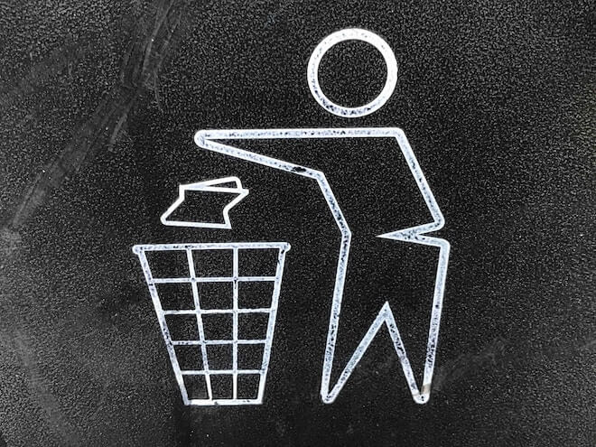 An illustration of a person throwing something into the trash bin