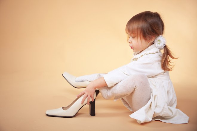 A little girl attempts to put on high heels