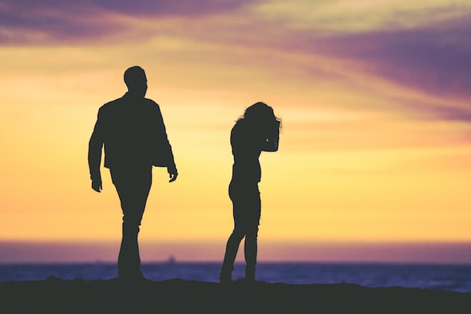 A man and a woman are silhouetted in front of a sunset