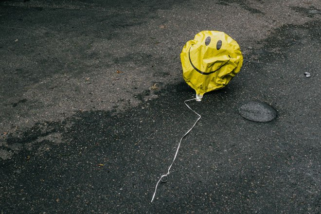 a deflated yellow smiley balloon on the street