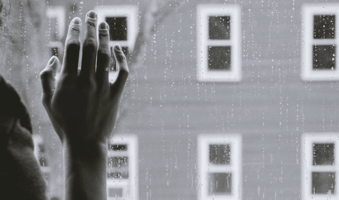 woman with hand pressed against rainy windowpane