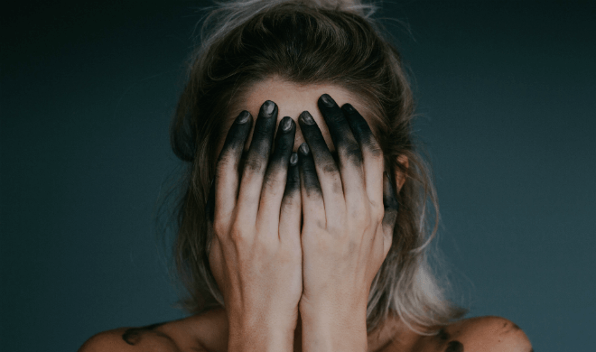 woman covering her face with her hands covered in black ink