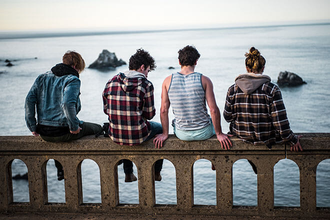 Teens sitting on a bridge