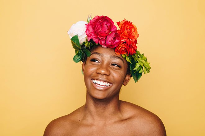 A smiling woman wears a crown of flowers