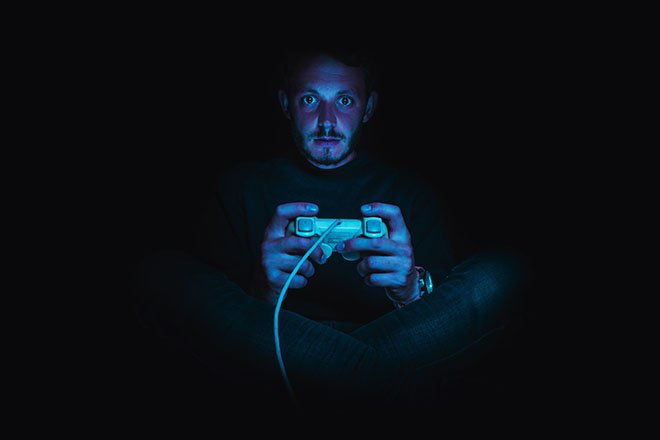 A man sits in the dark playing video games