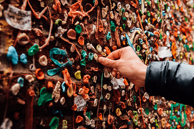 A man touching a wall of gum