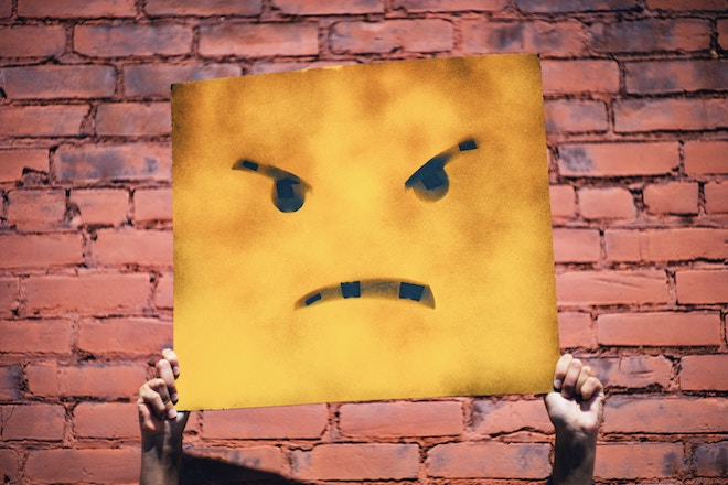 A man holds up a painted piece of cardboard with an angry face