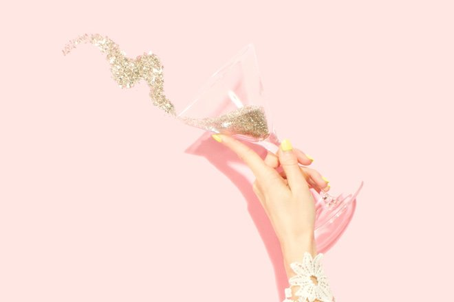 a woman's hand tips a champagne glass full of glitter
