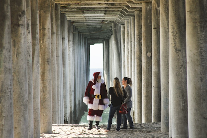 Two women meet a Santa under a California pier