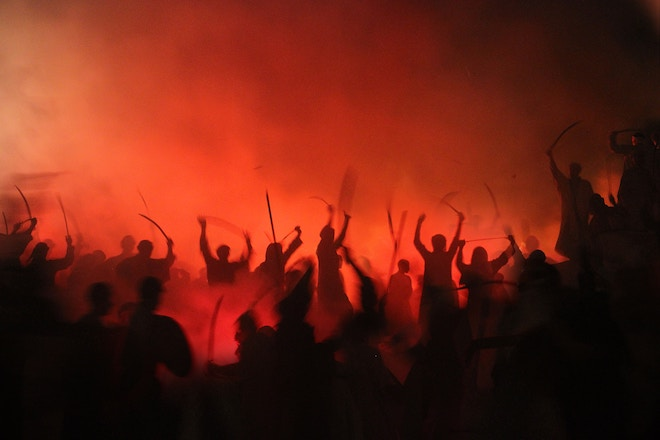 a mob of people surrounded by smoke and red light