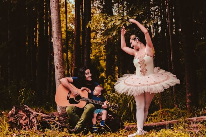 A man in the forest plays guitar while holding a child, next to a ballerina dancing