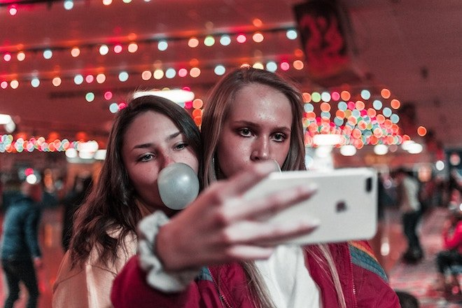 two women take a selfie while one blows a bubble