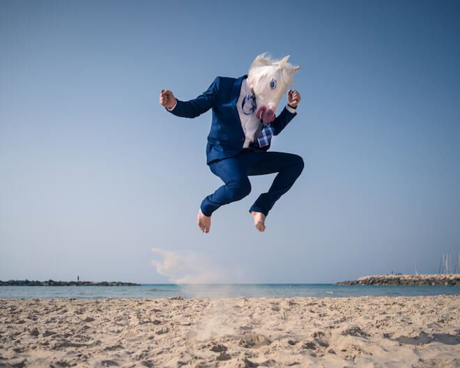A man in a horse mask jumps on the beach