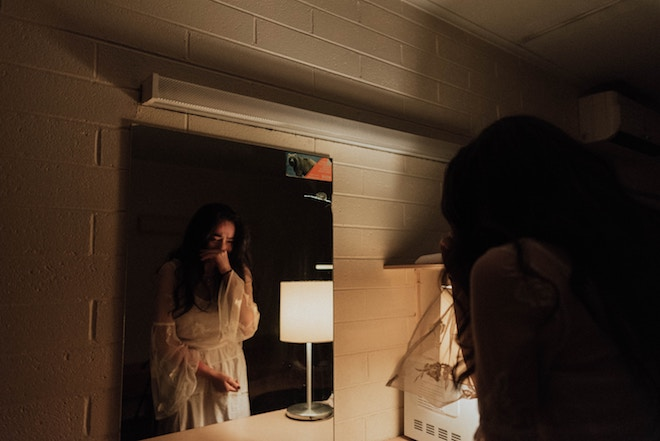 A woman cries while looking into the mirror.