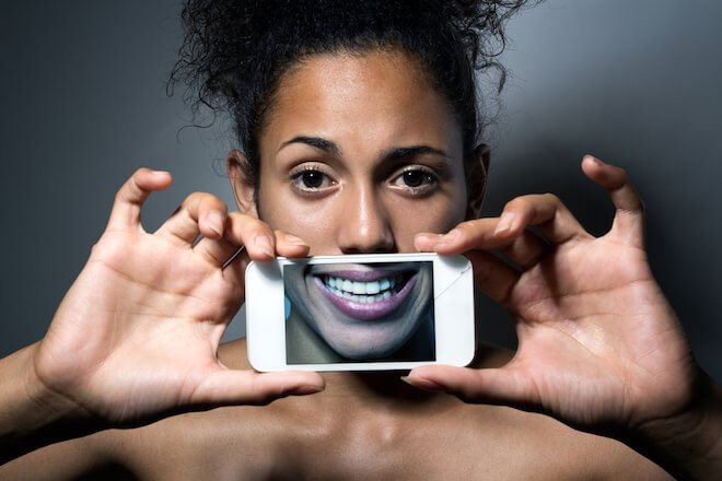 A woman holds a phone with a smile image in front of her mouth