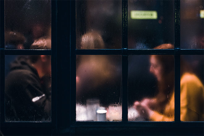 Couple sitting inside restaurant with foggy windows