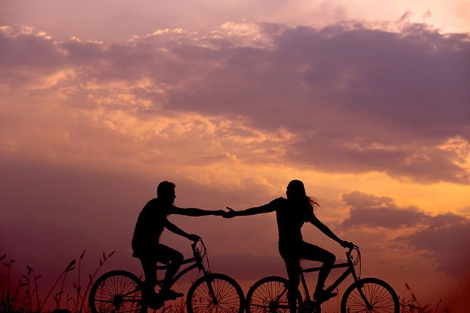Couple riding bikes at sunset