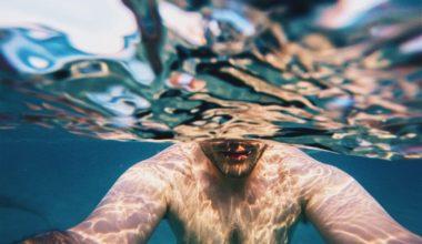man half under water holding camera