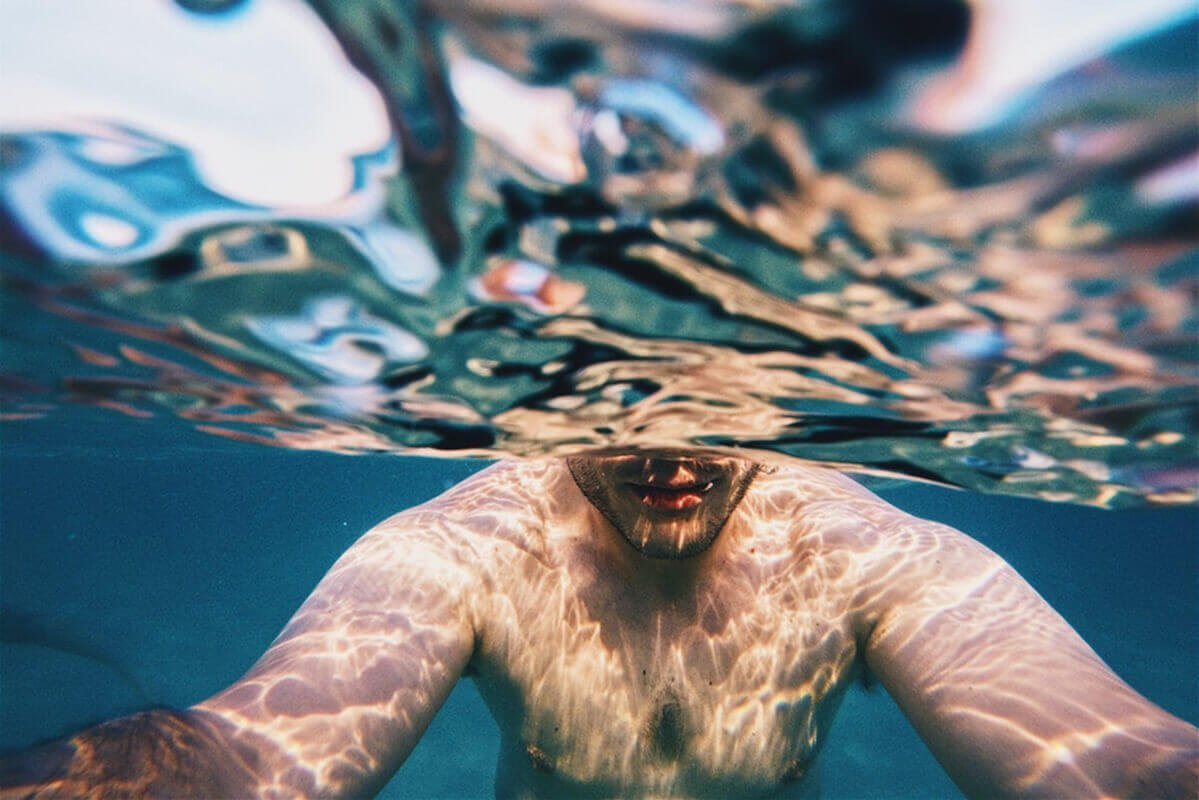 man half under water holding camera