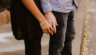couple standing front to back loosely holding hands