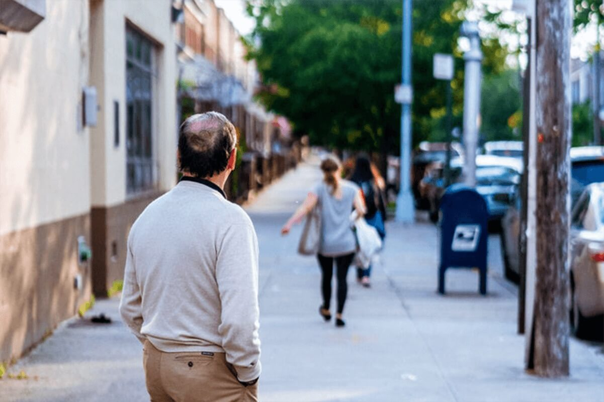 man looking down the sidewalk of a woman walking down the street