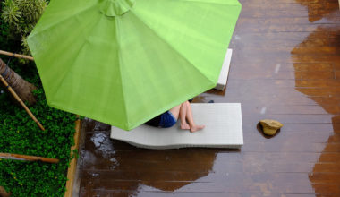 girl curled up under umbrella