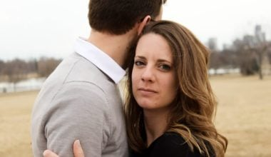 woman embracing male partner staring blankly toward camera