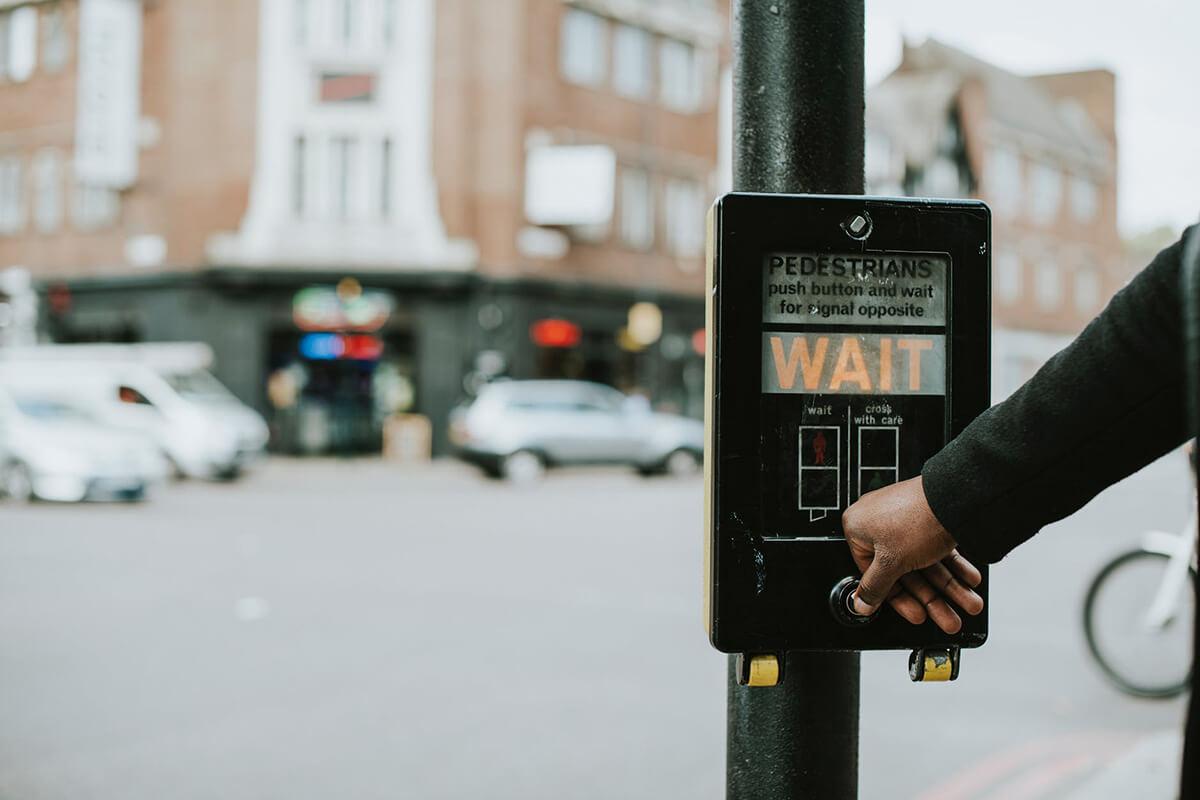 person pushing crosswalk sign that says wait
