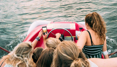 group of girls on a boat staring at a phone
