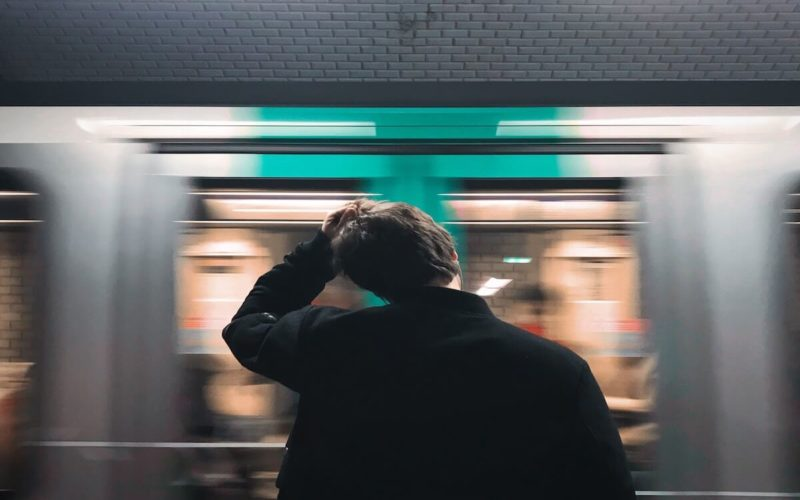 man waiting for the subway pulling his hair in stress