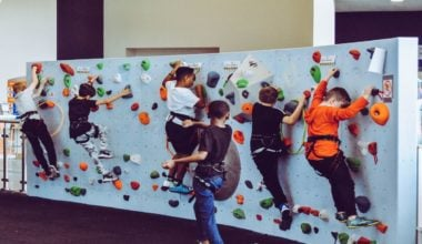 kids climbing up rock wall making progress