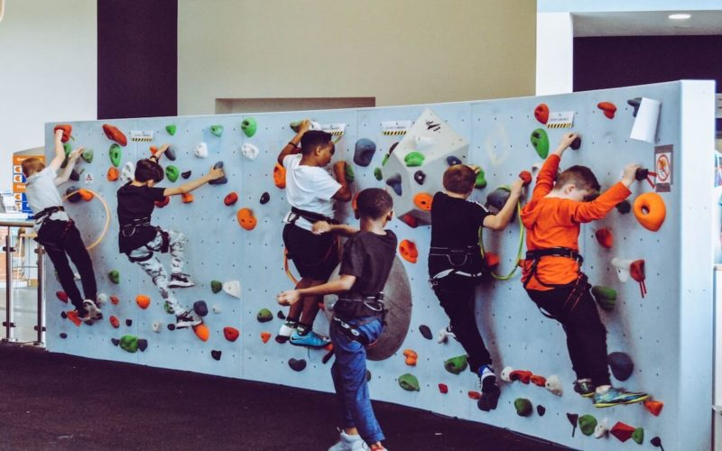 kids climbing up rock wall making progress