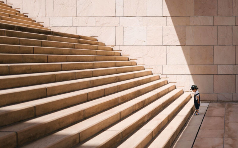 young boy staring up a large staircase