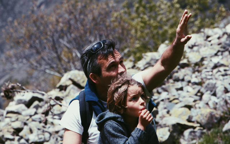 father hiking with son pointing upwards